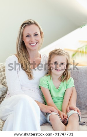 Mother and daughter sitting on the sofa together