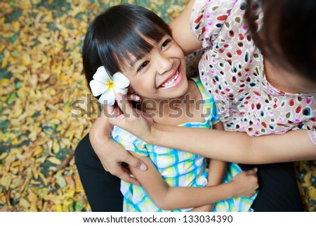 Mother and daughter sitting together in the park - stock photo