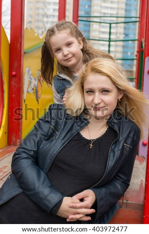 Mother and daughter sitting together on a playground.