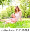 mother and daughter sitting together on the grass, and spend time with family - stock photo