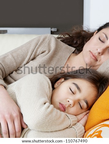 Mother and daughter sleeping on a white leather sofa at home. - stock photo