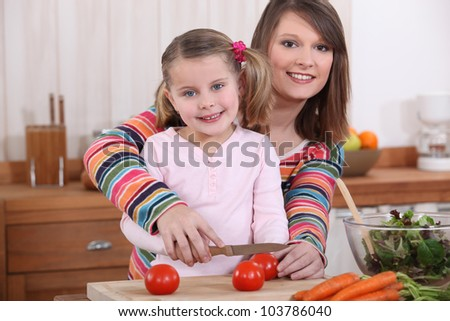 Mother and daughter slicing tomatoes