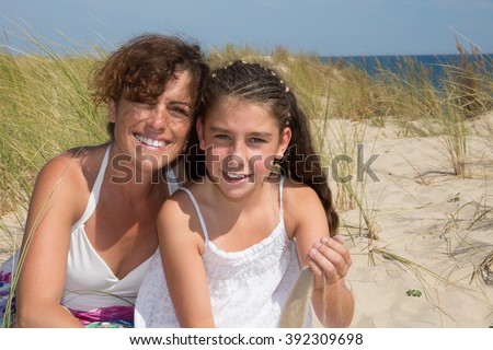 Mother and daughter smile at camera at the beach - stock photo