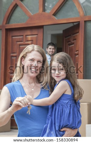 Mother and daughter smiling and holding the keys to their new house - stock photo
