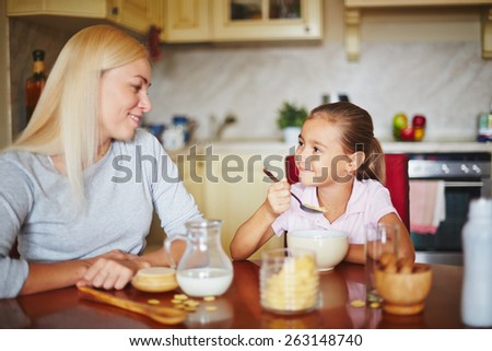 Mother and daughter smiling and looking at each other - stock photo