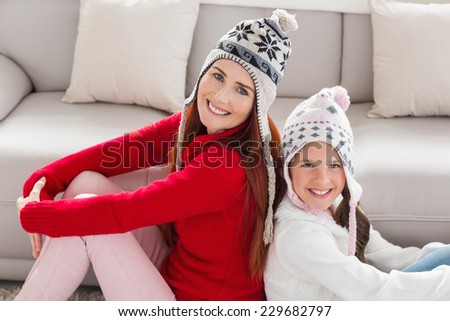Mother and daughter smiling at camera at home in the living room