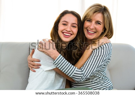 mother and daughter smiling at the camera at home - stock photo