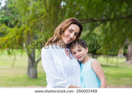 mother and daughter smiling at the camera on a park