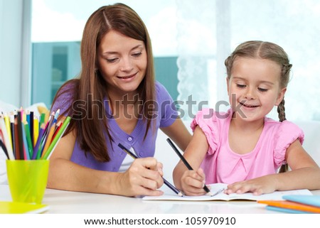 Mother and daughter spending time together at home drawing - stock photo