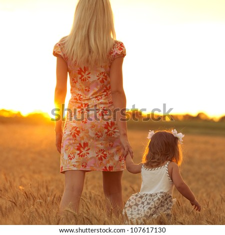 mother and daughter standing in a wheat field at sunset. outdoor shot - stock photo