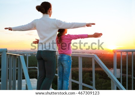 mother and daughter standing with arms outstretched to sides on roof of multistory building in evening and look at sunset.