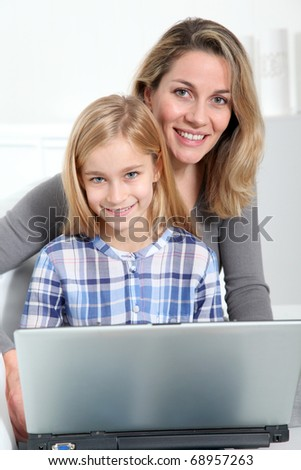 Mother and daughter surfing on internet - stock photo