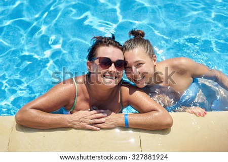 Mother and daughter swimming in the pool
