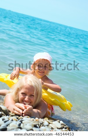 Mother and daughter swimming in the sea - stock photo