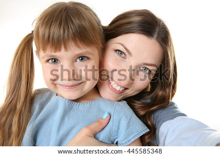 Mother and daughter taking selfie isolated on white