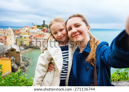 Mother and daughter taking selfie with smartphone having scenic view of colorful village Vernazza, Cinque Terre, Italy on background - stock photo