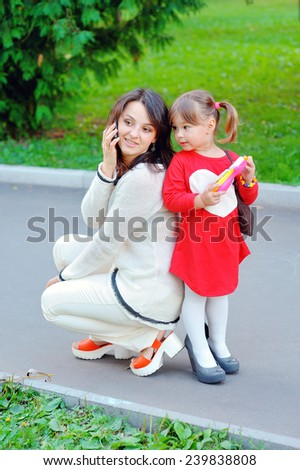 mother and daughter talk on the phone in the park. - stock photo