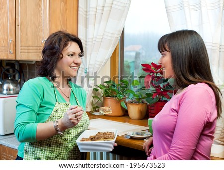 Mother and daughter talking, eating cake in kitchen