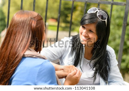 Mother and daughter talking holding hands teen smiling outdoors bonding - stock photo
