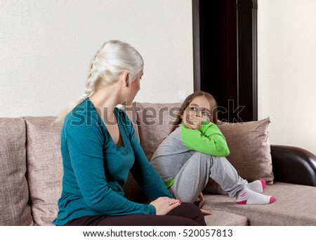 Mother and daughter talking on the couch