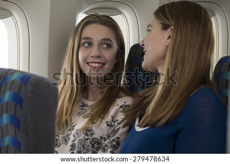 Mother and daughter talking with each other on an airplane - stock photo