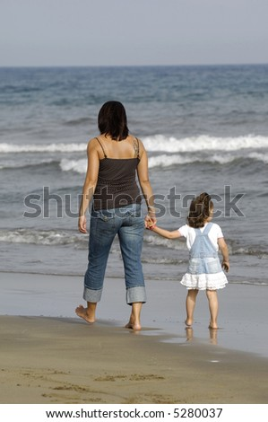 Mother and daughter together at the beach.