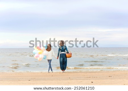 Mother and daughter together holding hands and contemplating on the summer beach. Summertime outdoors with blue cloudy sky background.