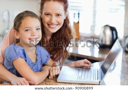 Mother and daughter together with notebook in the kitchen - stock photo