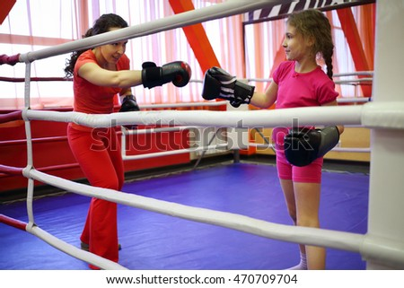 Mother and daughter train to boxing in ring in fitness center