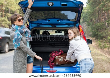 Mother and daughter traveling by car with suitcases in the spring. - stock photo