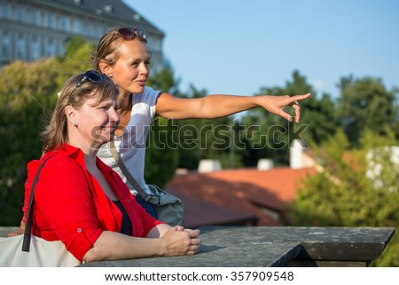 Mother and daughter traveling - two female tourists studying a map, discovering a new city - stock photo