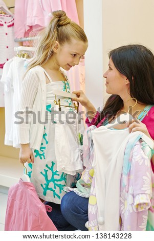 Mother and daughter try on clothes in clothing store - stock photo