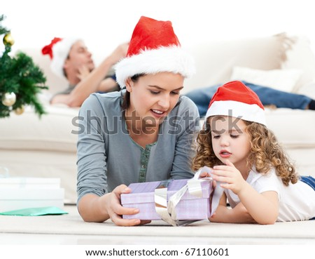 Mother and daughter unwrapping a present lying on the floor in the living room - stock photo