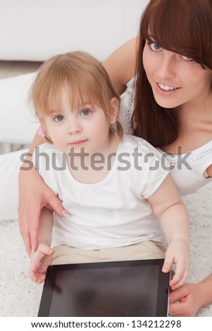 Mother and daughter using a tablet pc - stock photo