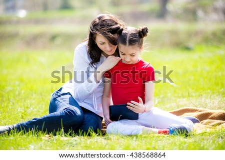 Mother and daughter using digital tablet while sitting in the beautiful nature,Mother and daughter using digital tablet