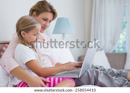 Mother and daughter using laptop in bed at home in the bedroom - stock photo