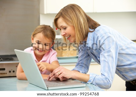 Mother and daughter using laptop in domestic kitchen - stock photo