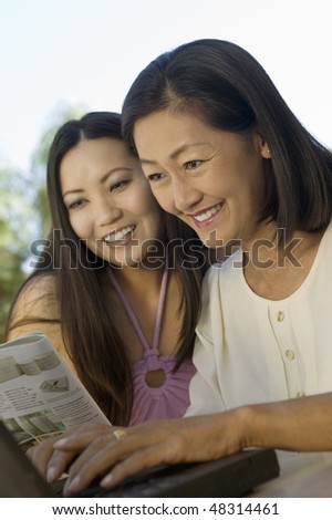 Mother and Daughter Using Laptop Together - stock photo