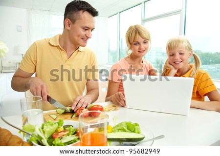 Mother and daughter using laptop while father cutting fresh vegetables - stock photo