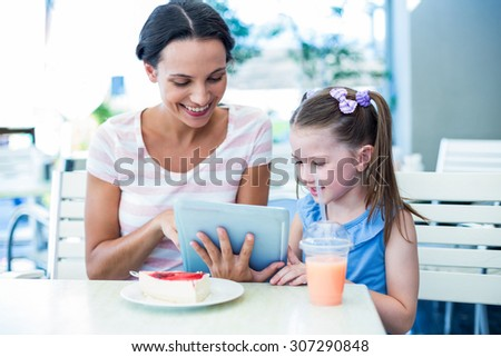 Mother and daughter using tablet computer together in a restaurant - stock photo