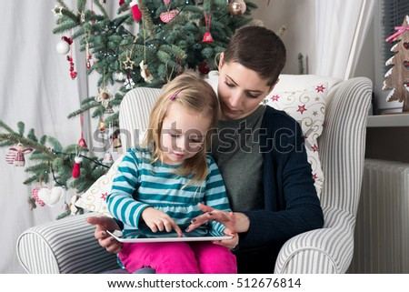 Mother and daughter using tablet PC near Christmas tree
