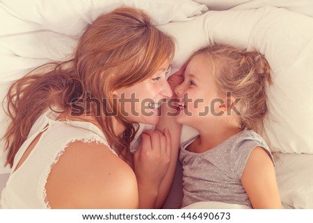mother and daughter waking up with a smile