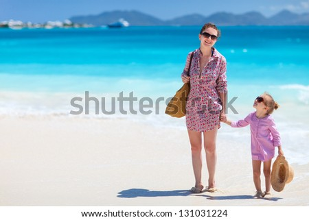 Mother and daughter walking along a tropical beach