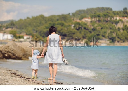 mother and daughter walking away on beach - stock photo