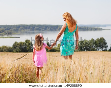 Mother and daughter walking  in summer field near lake on a sunny day - stock photo