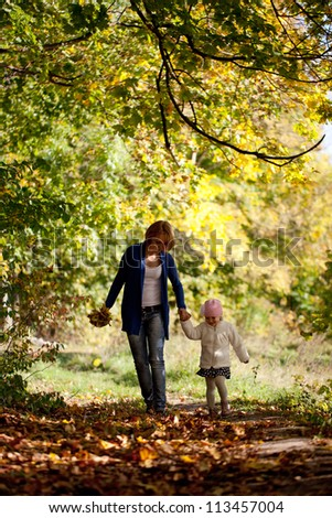 Mother and daughter walking in the autumn forest - stock photo