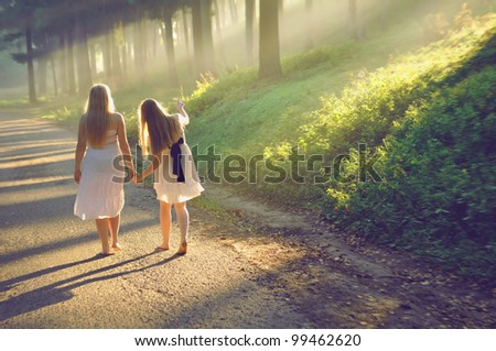 mother and daughter walking in the forest and holding hands