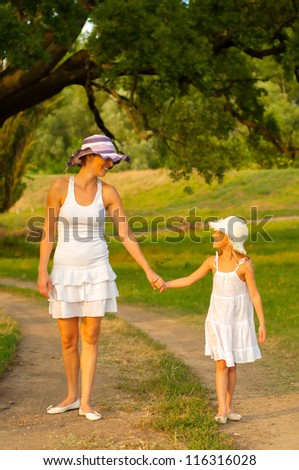 Mother and daughter walking in the nature on beautiful summer day. - stock photo
