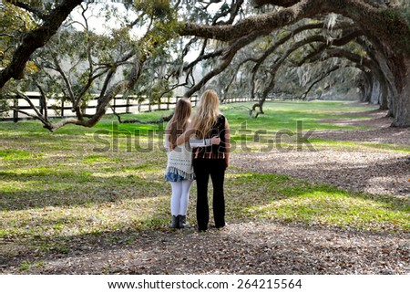 Mother and daughter walking in the park, beautiful oak trees in the background.  - stock photo
