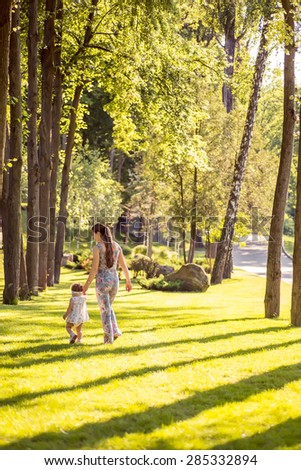 mother and daughter walking in the park, happy summer  - stock photo